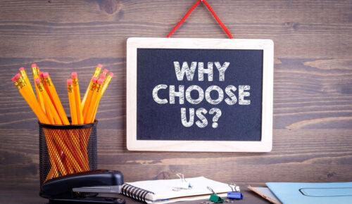 Why choose us? Chalkboard on a wooden background